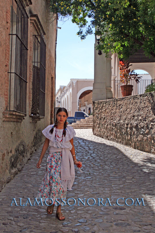 A girl walking along a cobblestone alley in Alamos, Sonora
